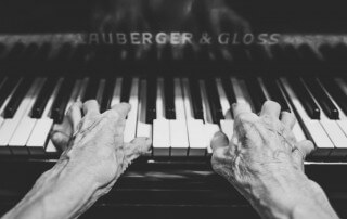 Hands of an older person playing the piano