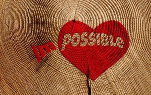 Red heart on wood with words im - possible